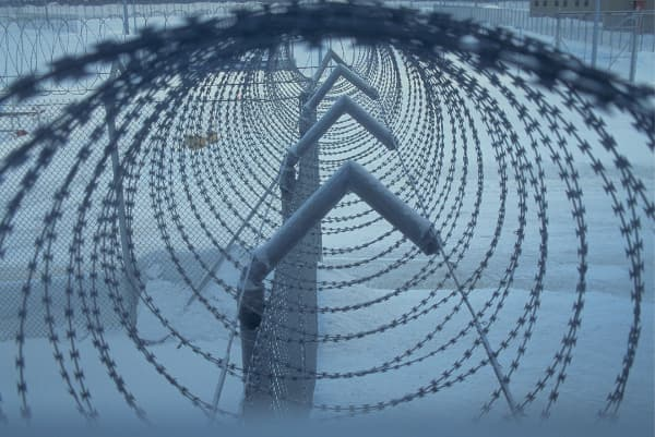 A barbed-wire fence with cameras on top at a prison.